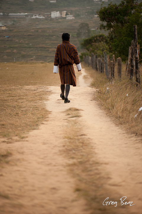 Man in Bhutanese gho walking down a path