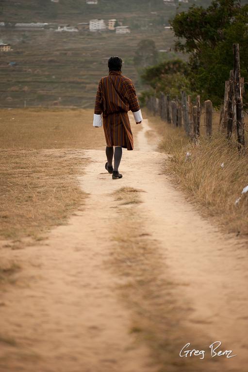 Man in Bhutanese gho walking down a path