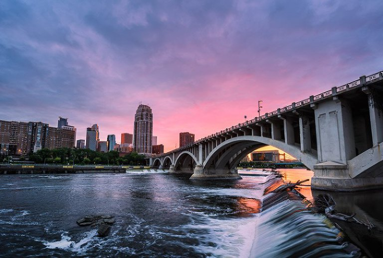 The Carlyle Building and 3rd Ave Bridge in downtown Minneapolis with a beautiful pink sunset skyline