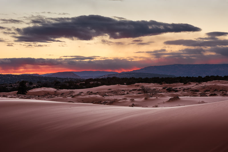 A firey red sunset over sweeping sand dunes