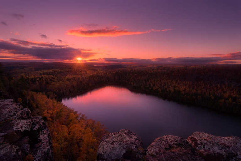 A pink and purple sunset reflected in a lake as viewed from a rocky ledge