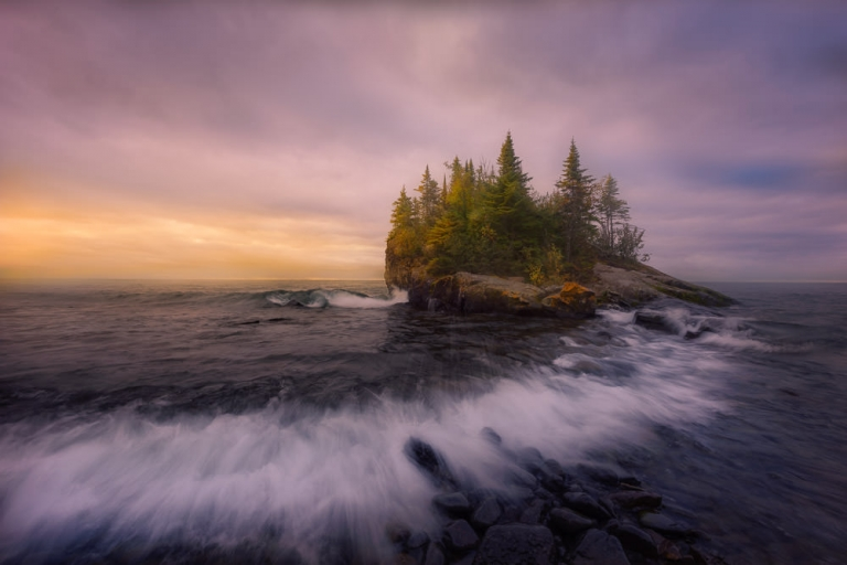 Waves from Lake Superior crash into a small rocky island of evergreen trees and the North Shore of Minnesota during a golden yellow and cloudy sunset