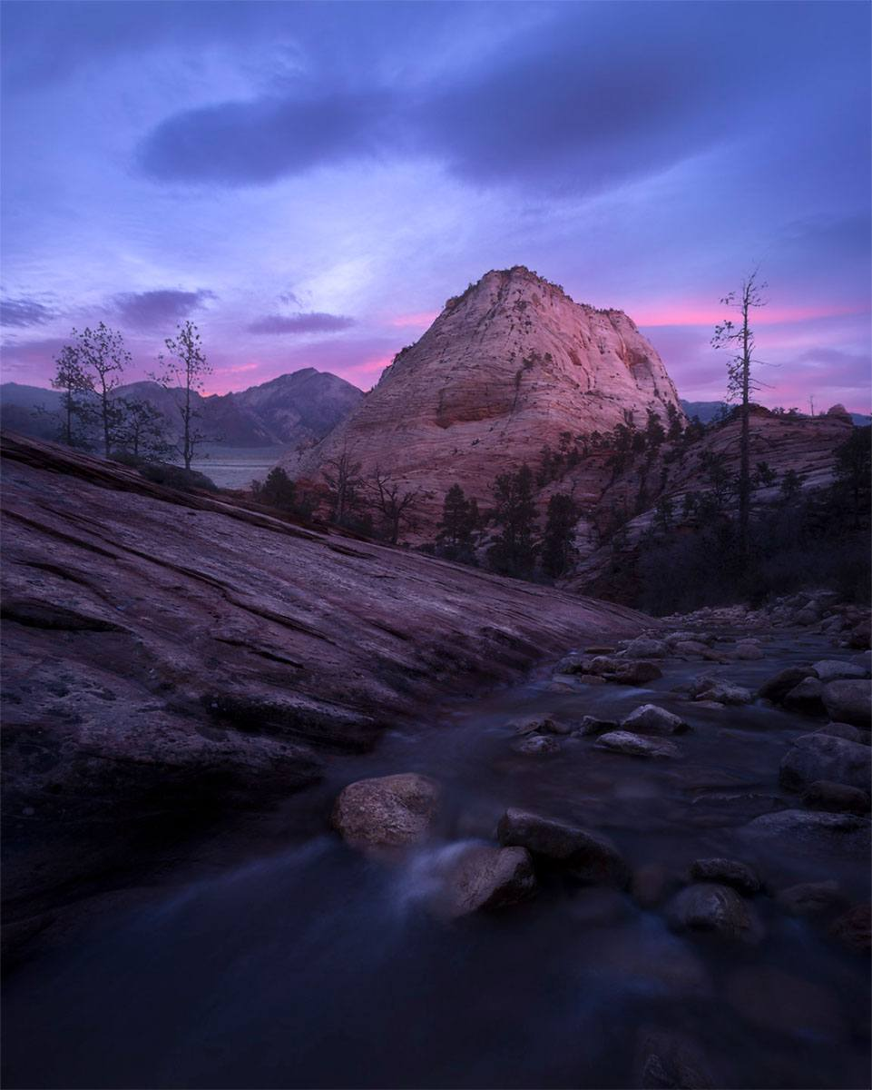 Pink sunset and mountain over a flowing stream