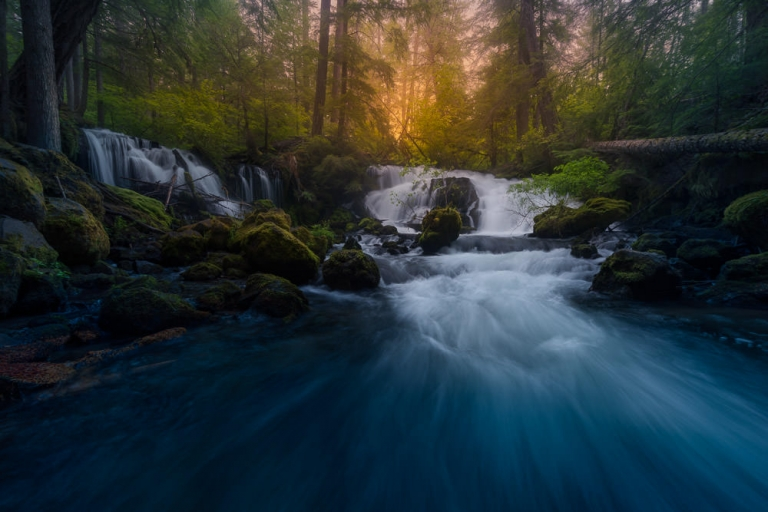 Twin Waterfalls cascading through a forest at sunset