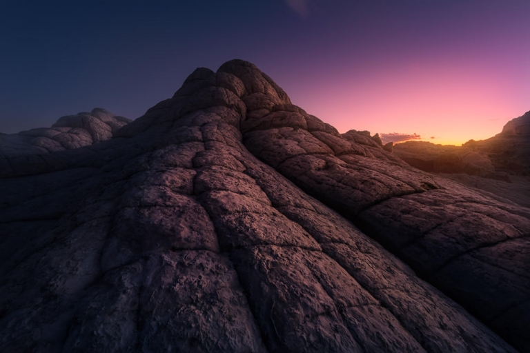 A Pink Sunrise Over a Mountain Made of Sandstone Hexagons